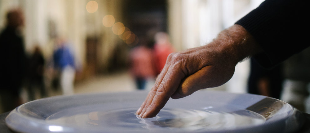 Hand in Weihwasser