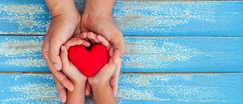 Kinderhände mit Herz in Erwachsenenhände