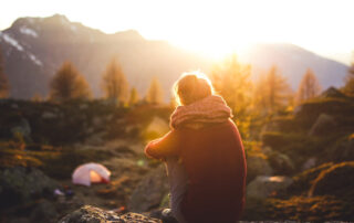 Frau sitzend im Sonnenuntergang